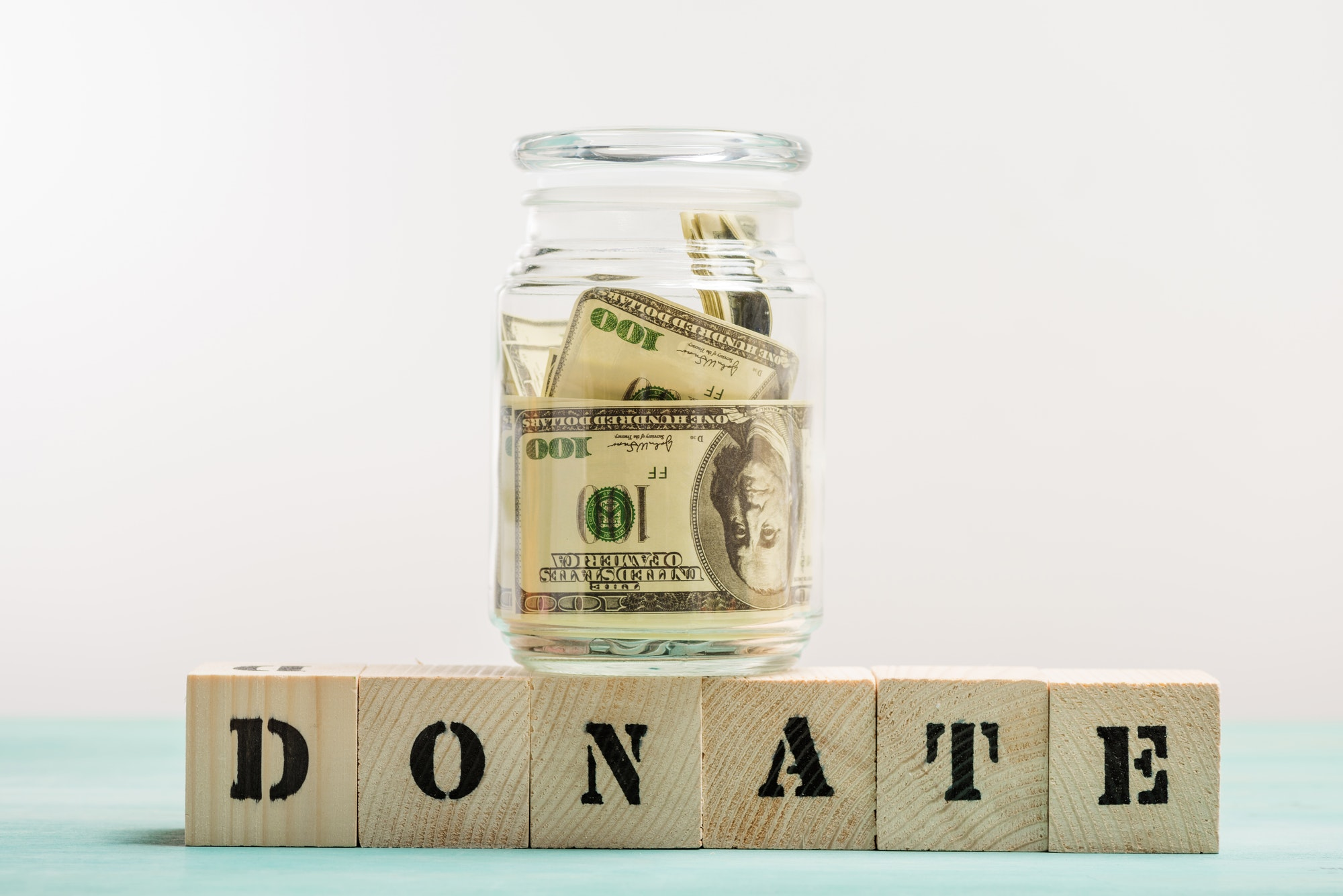 Dollar banknotes in glass jar and wooden cubes with donate lettering, donation concept